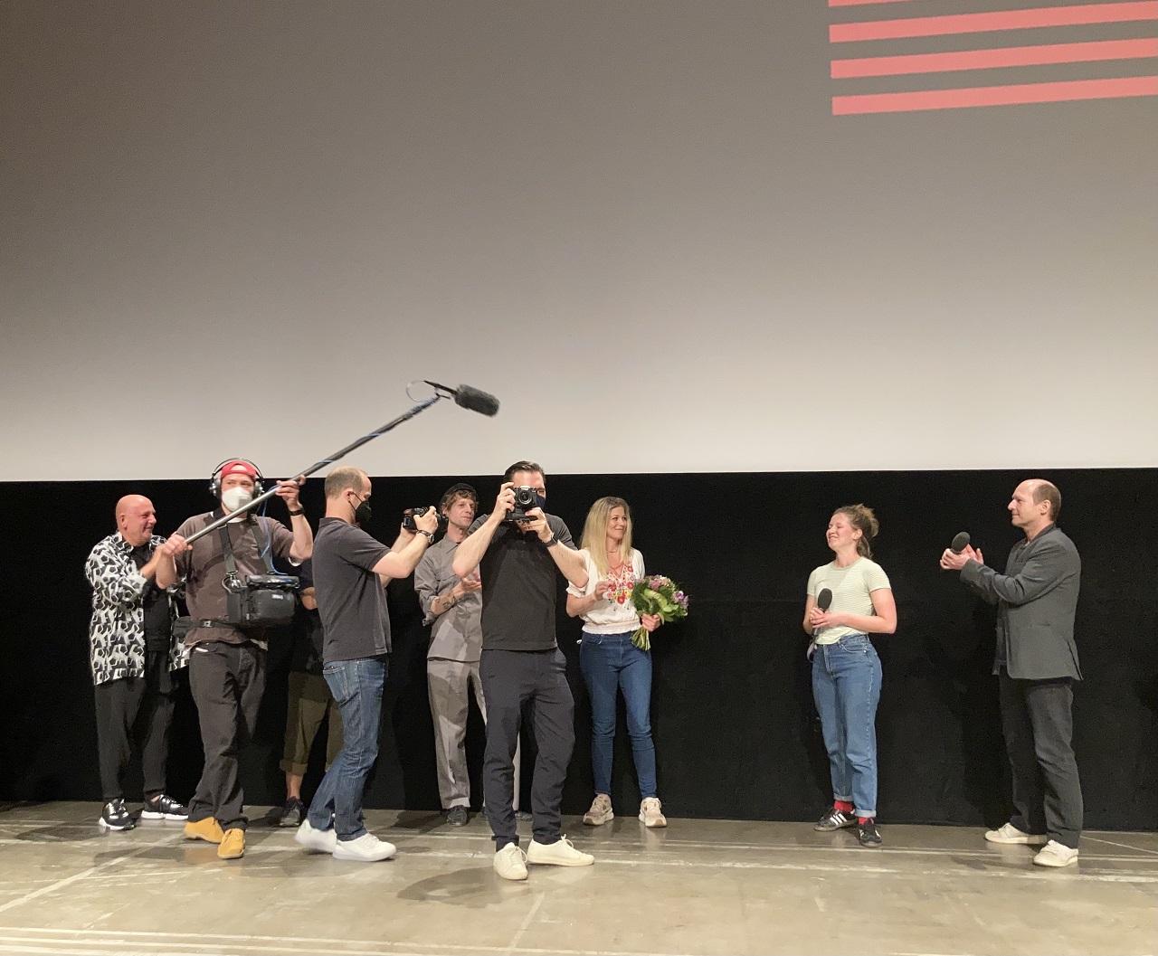 """Sebastian Brauneis und das Diagonale-Preisrevue-Team überraschen Hilde Dalik nach der Vorführung von """"Sargnagel - der Film"""" mit dem Preis als beste Darstellerin der Diagonale 2021."""