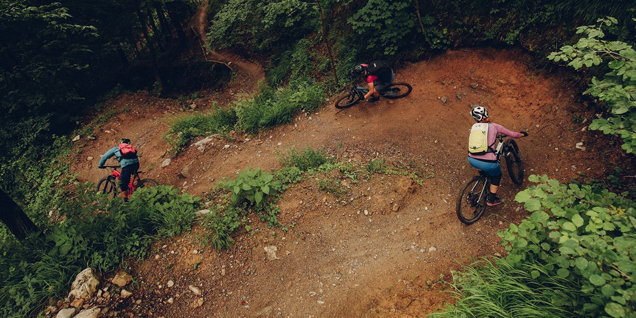 Mountainbiker*innen fahren einen kurvigen Trail