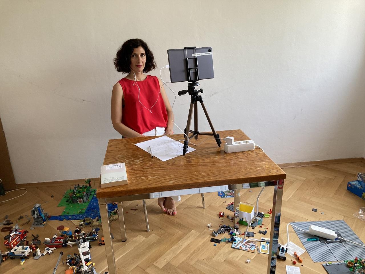 Nava Ebrahimi bei ihrer Lesung für die 45. Tage der deutschsprachigen Literatur. Sie sitzt an einem Schreibtisch, auf dem Boden liegt Lego.