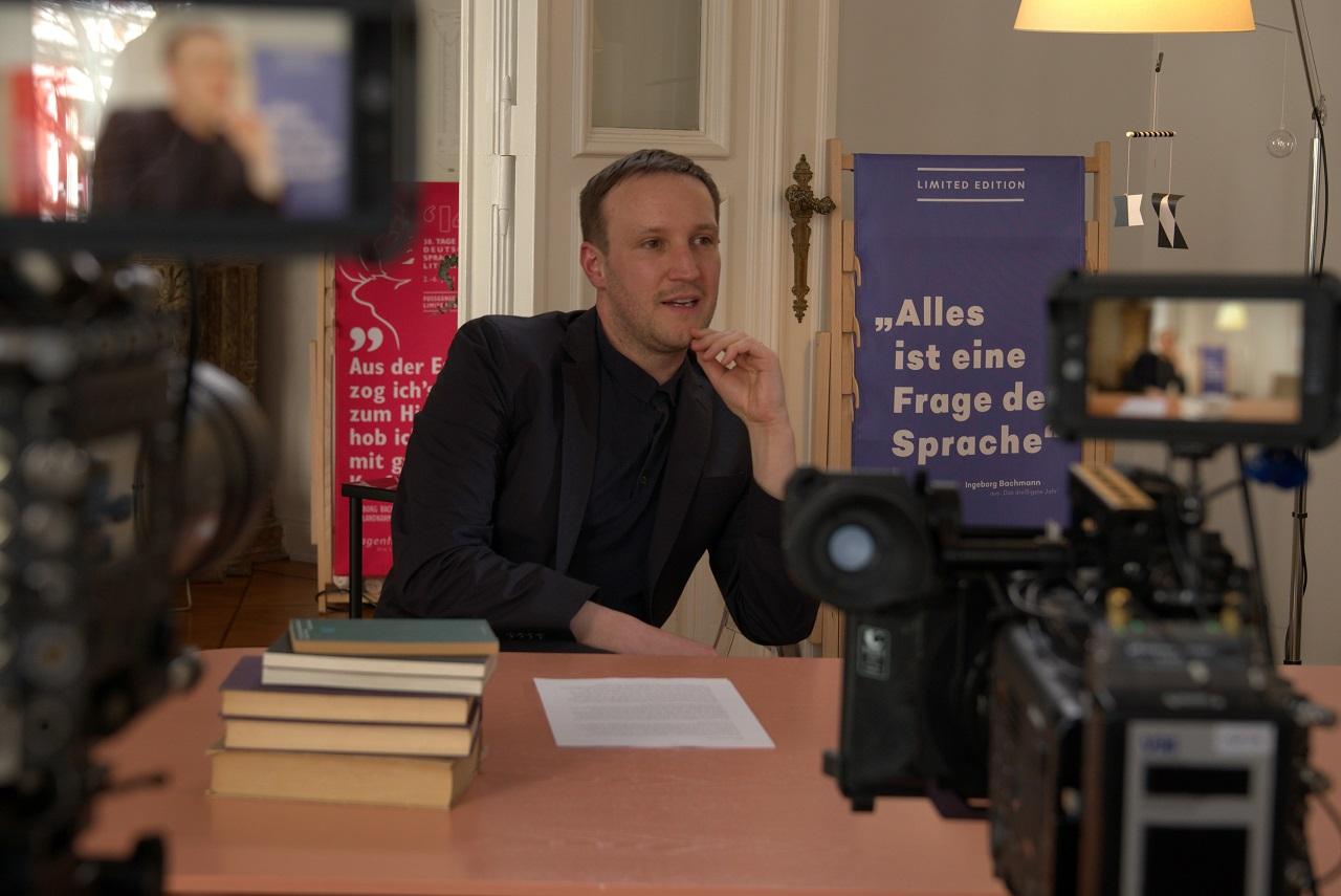 Timon Karl Kaleyta sitzt an einem Schreibtisch bei seiner Lesung für den Bachmannbewerb.