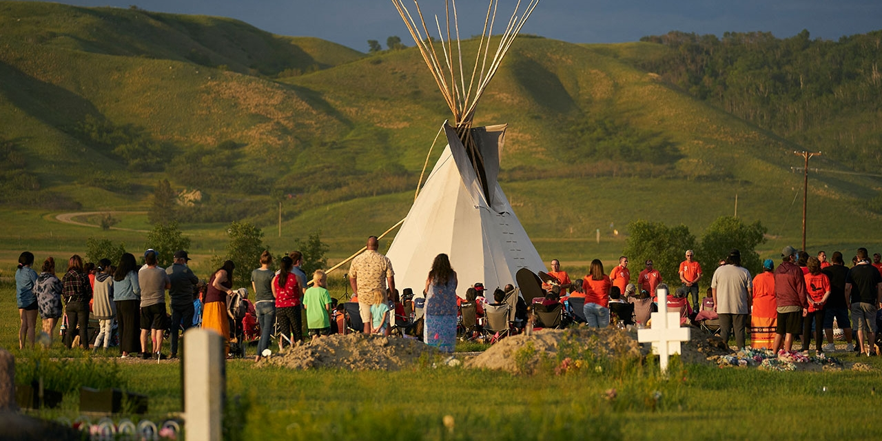 Hundreds of people gather for a vigil in a field where human remains were discovered in unmarked graves at the site of the former Marieval Indian Residential School