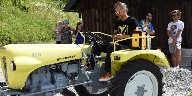 FM4-Traktorgewinner Andreas sitzt auf dem Traktor am Hof.