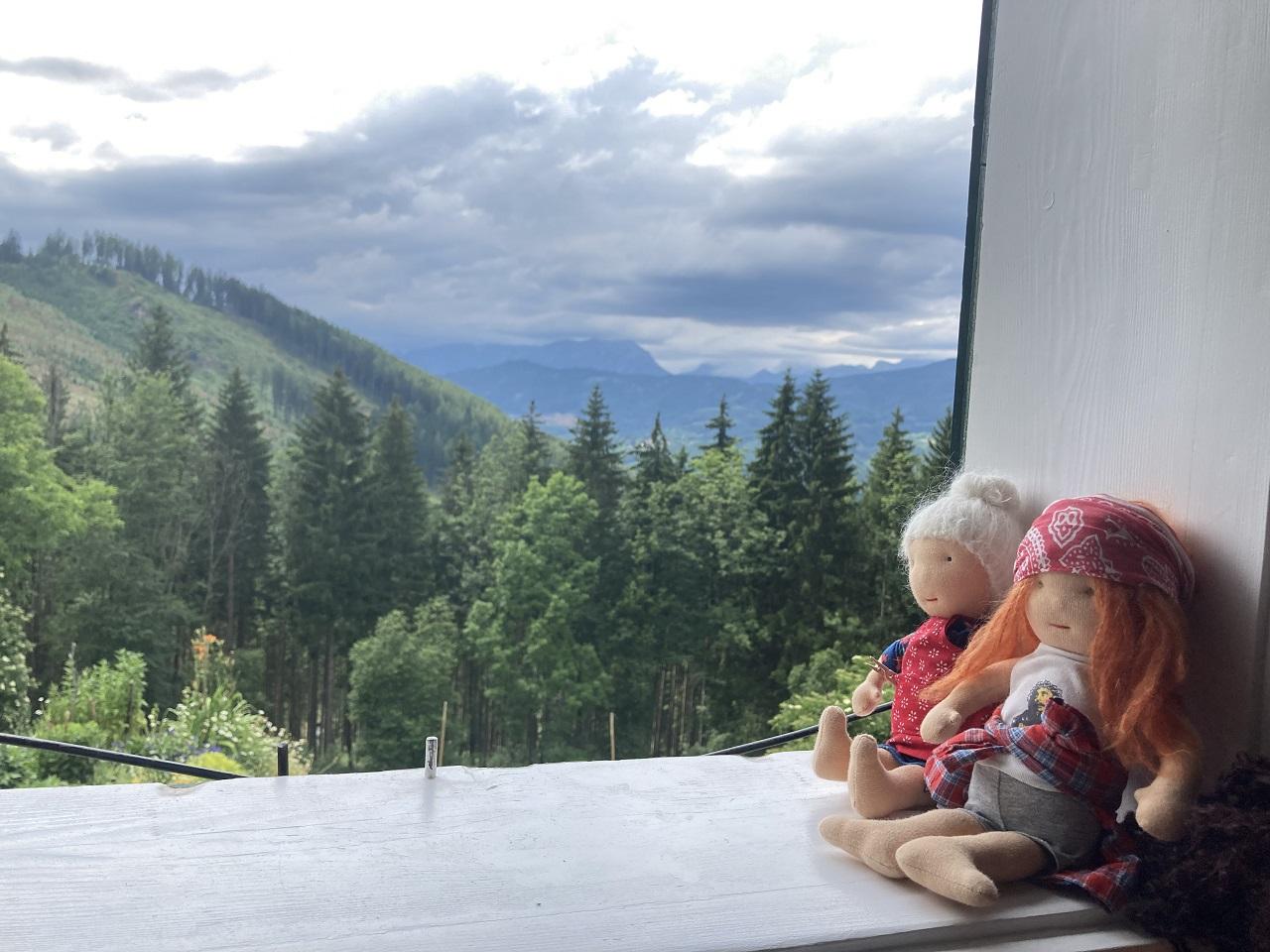 Zwei Stoffpuppen von Alexandra Hagemann, eine mit grauem Dutt und Brille, eine wie Axl Rose sitzen im Fenster, dahinter ein schönes Bergpanorama