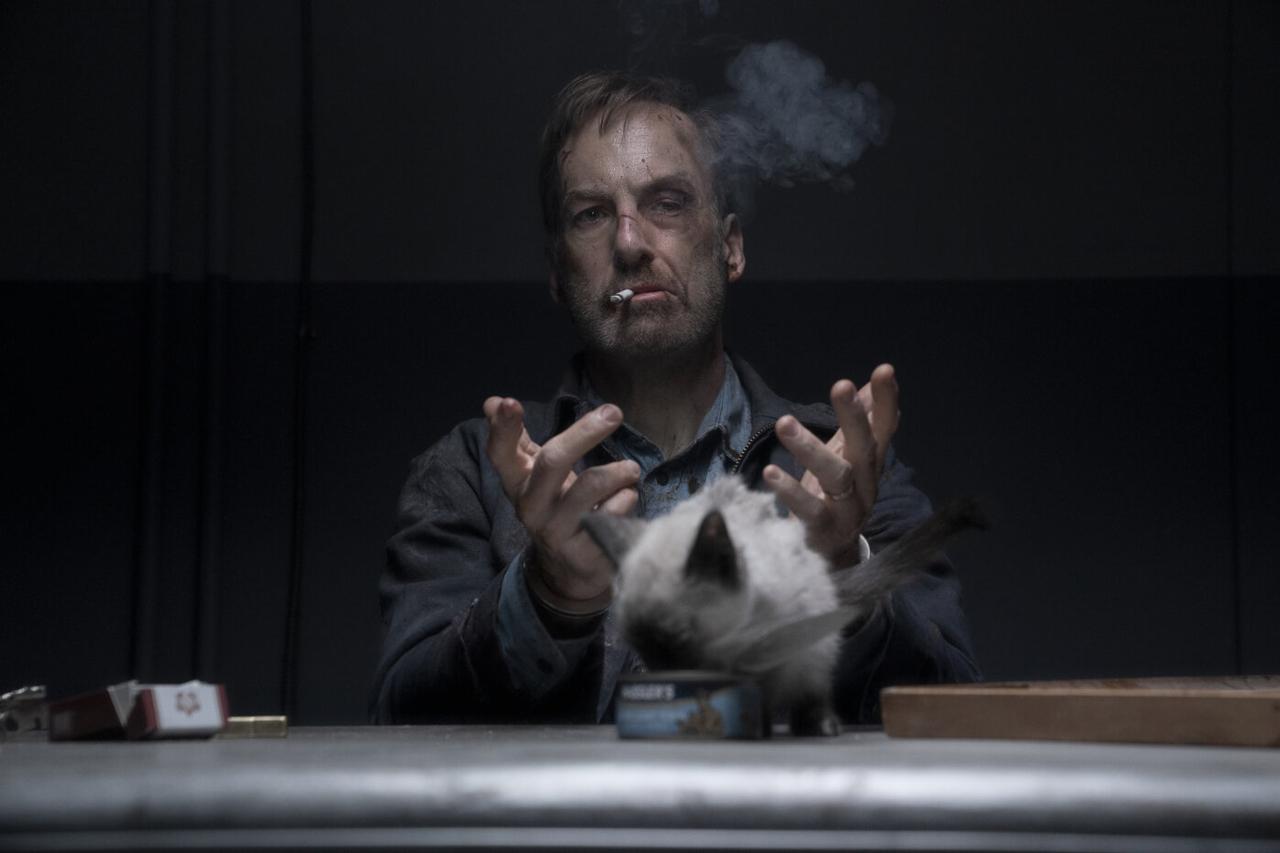 Ein Mann mit Schnittwunden im Gesicht sitzt an einem Tisch, raucht und gestikuliert. Vor ihm sitzt eine Katze und frisst aus einer Dose.