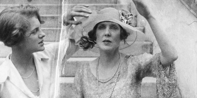 Zwei Frauen, eine richtet der anderen den Hut.