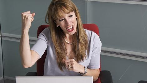 Eine Frau freut sich vor einem Laptop