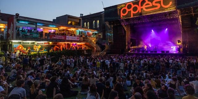 Popfest Arena Wien Tag 1 Konzert Eli Preiss, Publikum sitzt und tanzt auf der Wiese, die Sonne geht unter