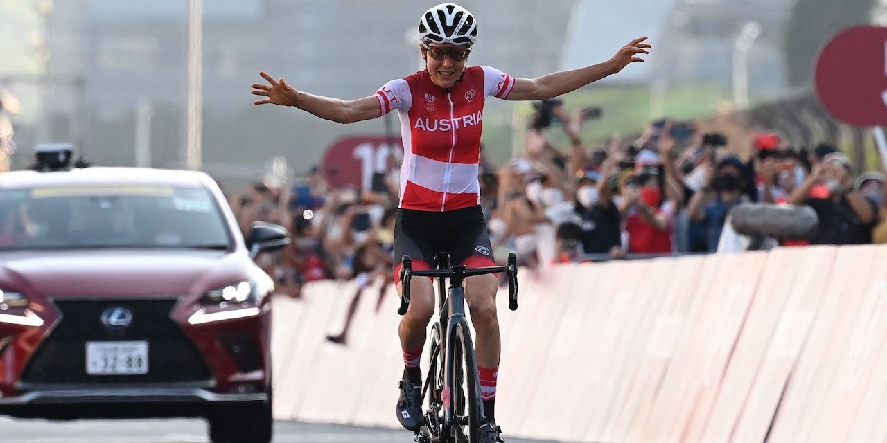 Austria's Anna Kiesenhofer celebrates as she crosses the finish line to win the women's cycling road race of the Tokyo 2020 Olympic Games
