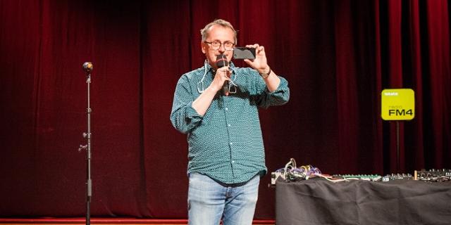 Martin Blumenau mit Smartphone auf Bühne