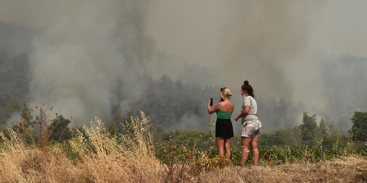 Zwei Frauen schauen auf ein Handy und auf den vielen Rauch, der vor ihnen aufsteigt