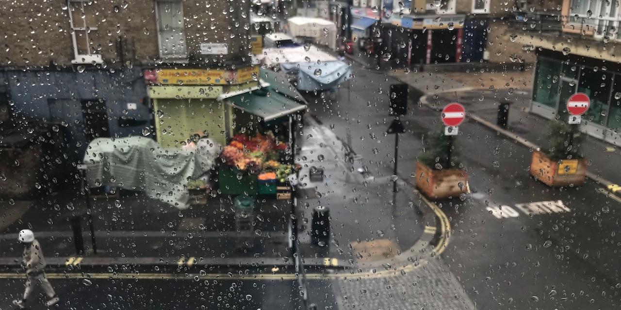 Blick auf Londoner Straße durch regennasses Fenster