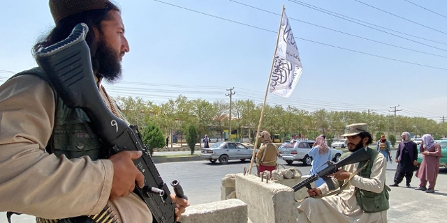 Taliban fighters stand guard at an entrance gate outside the Interior Ministry in Kabul on August 17, 2021