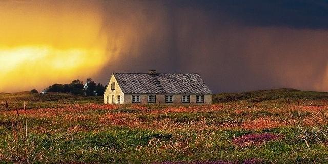 Ein Bauernhaus steht auf dem Feld, im Himmel darüber entsteht ein Sturm