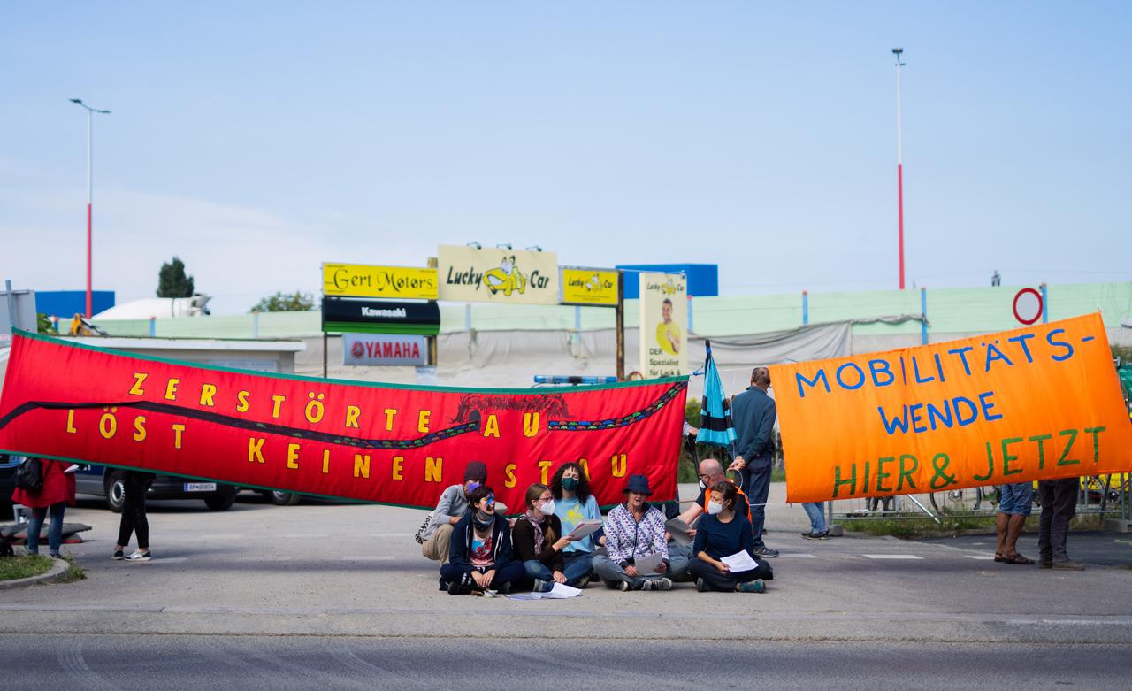 """Eine Gruppe von Klimaaktivistinnen und Aktivisten mit zwei Transparenten: """"Zerstörte Au löst keinen Stau"""" und """"Mobilitätswende hier und jetzt"""""""
