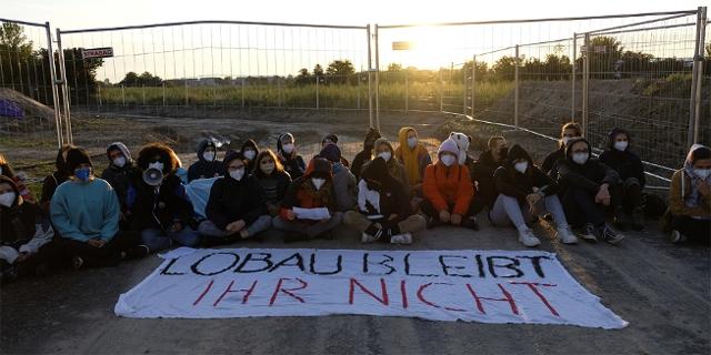 """Eine Gruppe von Klimaaktivistinnen und Aktivisten sitzt vor einem Transparent mit der Aufschrift: """"Lobau bleibt - ihr nicht"""""""