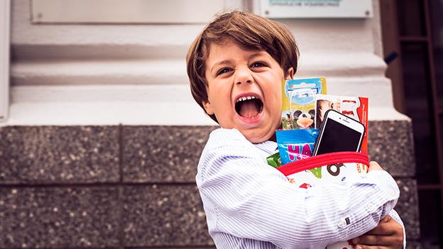 Kind mit Smartphone in der Schultüte
