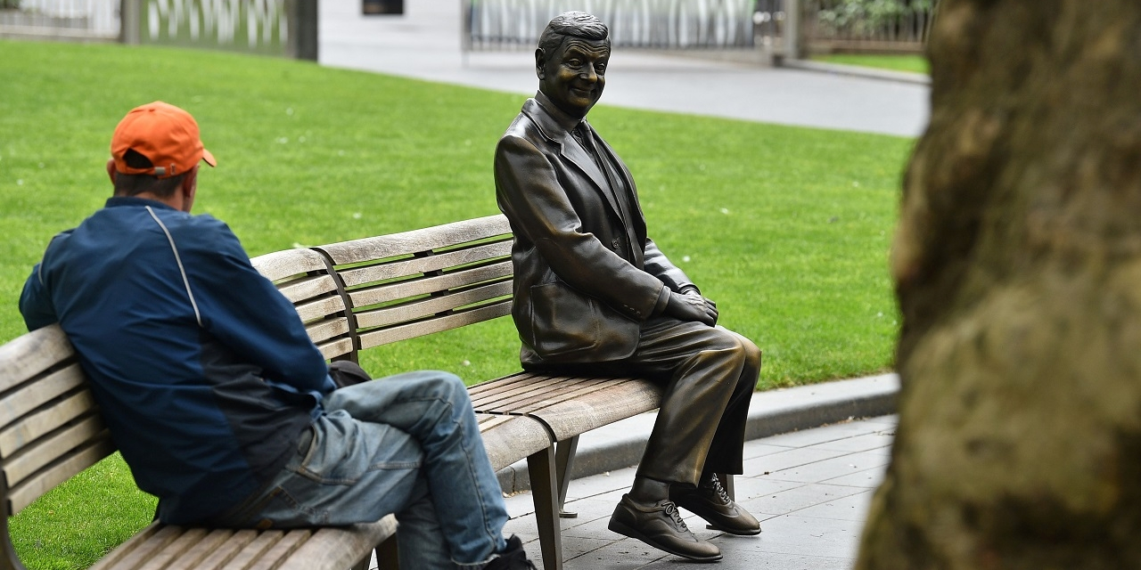 A man sits beside a statue of comedian Rowan Atkinson in Leicester Square in London on May 3, 2020