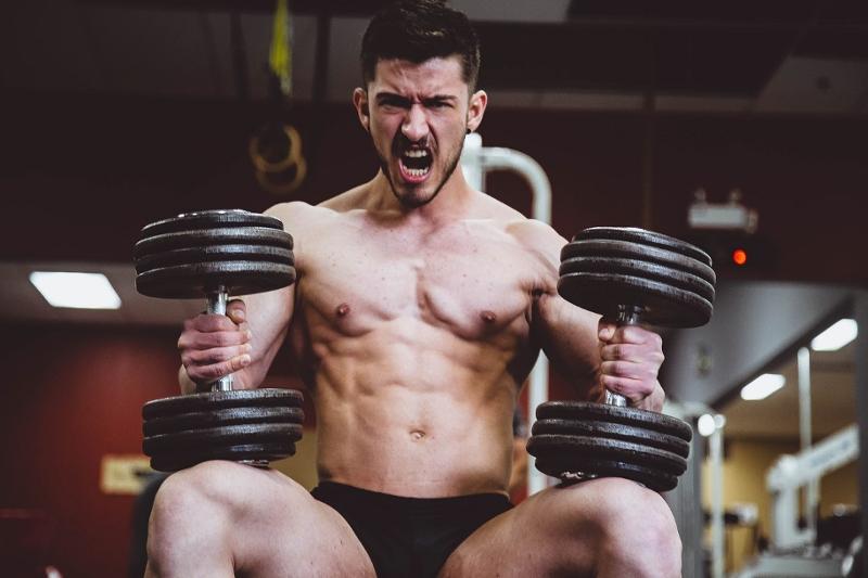 Mann mit nacktem Oberkörper und Gewichten