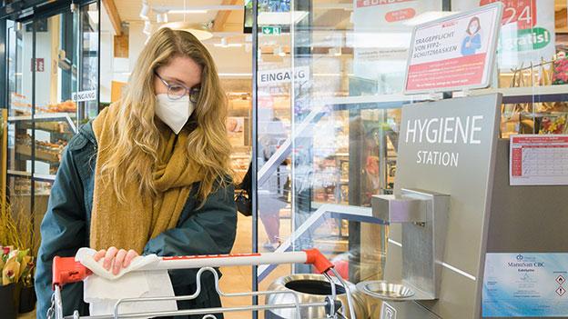 Frau im Supermarkt beim Desinfizieren