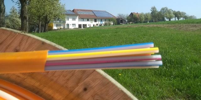 Bunte Glasfaserkabel vor ländlicher Idylle