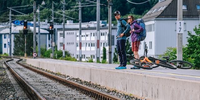 Zwei Bergsportler*innen warten am Bahnsteig