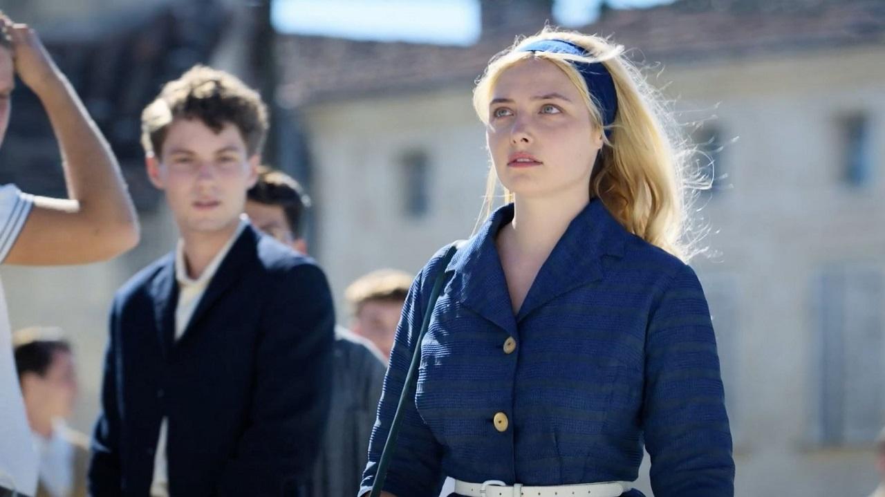 """Ein Bursche und ein sehr schönes Mädchen (Lula Cotton-Frapier) gehen über den Schulhof. Szene aus der Serie """"Voltaire High""""."""