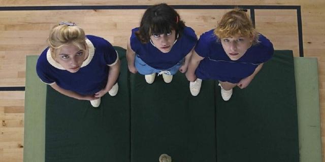 """Drei Mädchen im Turnsaal, sie schauen zu einem Seil hinauf. Szene aus der Serie """"Voltaire High"""""""