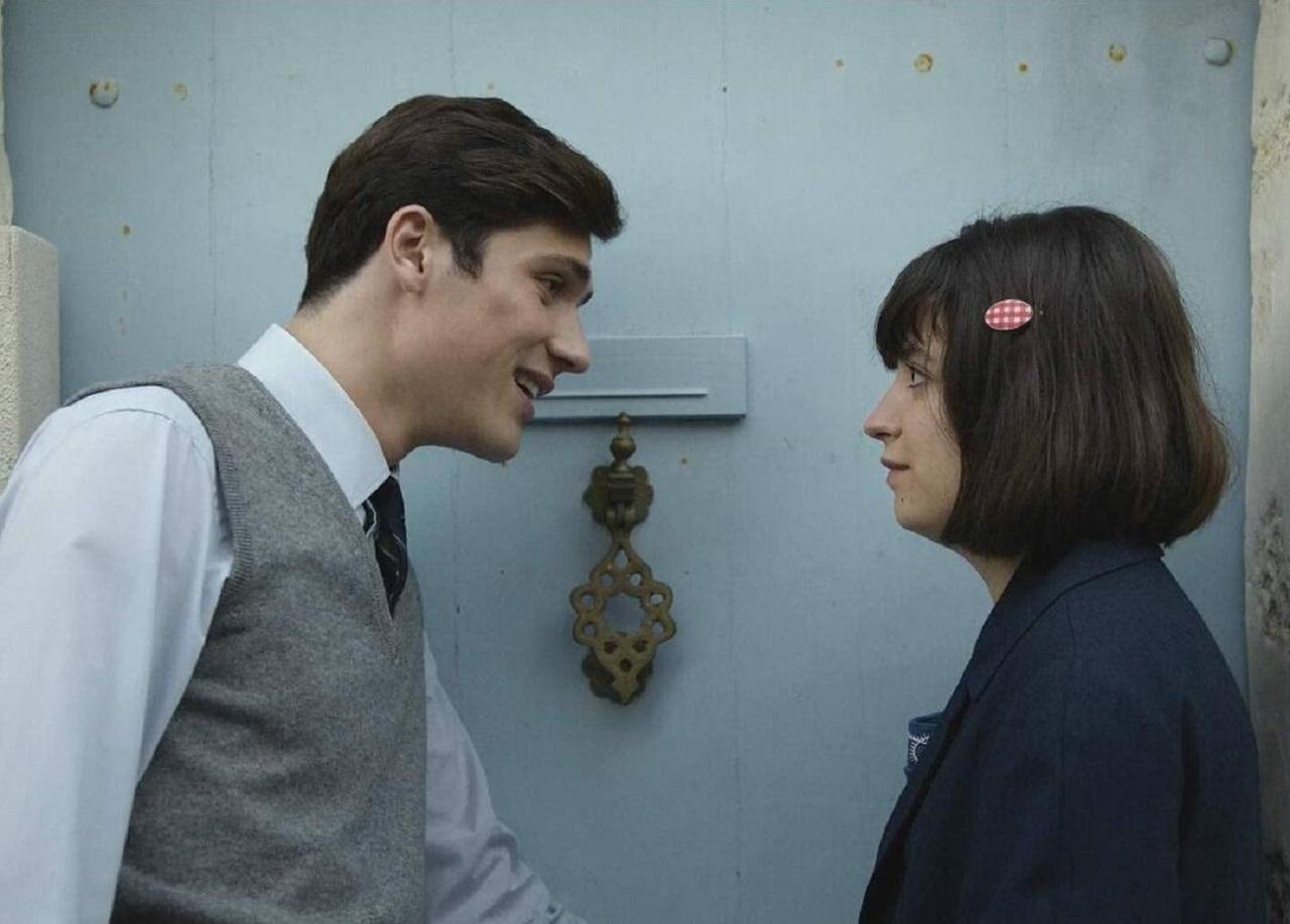 """Junger Mann in Hemd und Weste beugt sich zu einer jungen Frau mit Spange im Bob. Szene aus """"Voltaire High""""."""