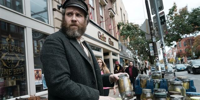 """Seth Rogen in einer Szene aus """"An American Pickle"""", altmodisch gekleidet auf einer Straße im heutigen New York, mit einem Leiterwagerl voll Gurken in Gläsern."""