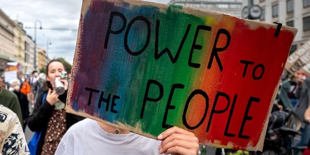 """Demo-Teilnehmer*in hält Schild mit der Aufschrift """"Power to the People"""""""
