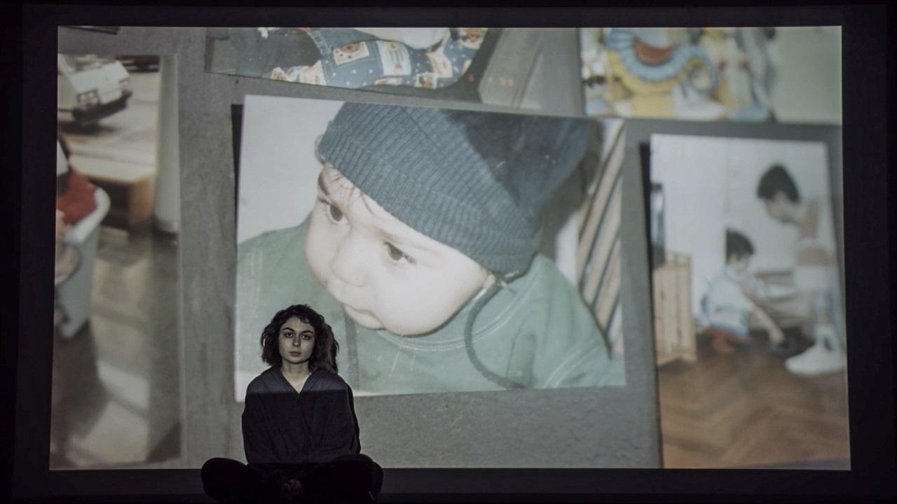 Eine junge Frau sitzt vor einer Wand, auf der ein Foto aus der Kindheit projiziert ist.
