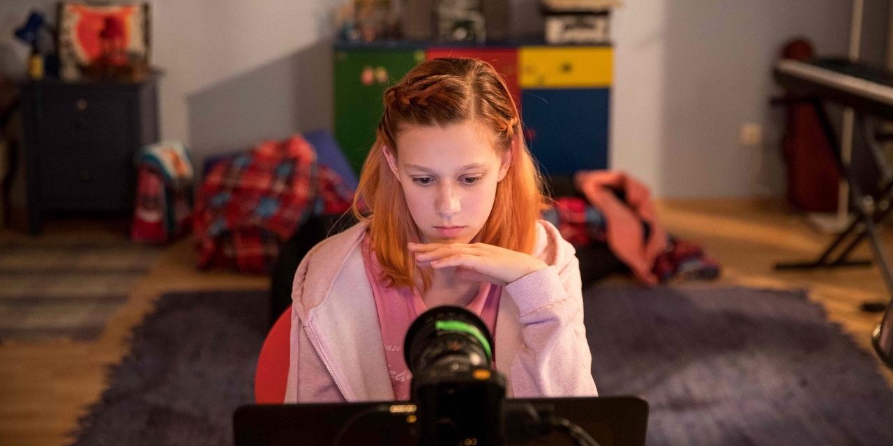 Eine Schauspielerin, die wie ein junges Mädchen aussieht, vor einem Computer in einem Filmstudio.