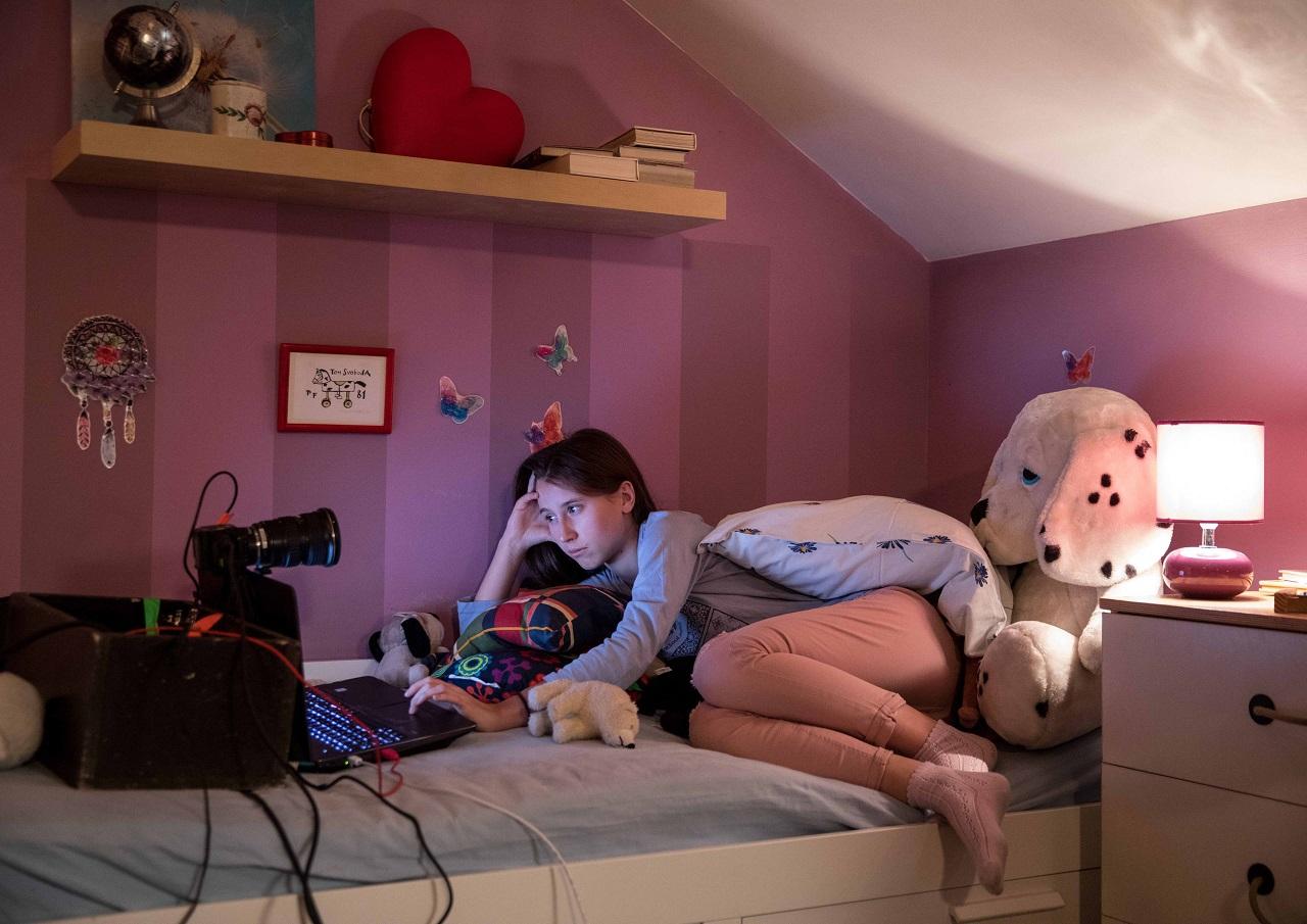 """Eine Darstellerin beim Chatten im Kinderzimmer-Set. Sie spielt eine 12-Jährige in """"Gefangen im Netz""""."""