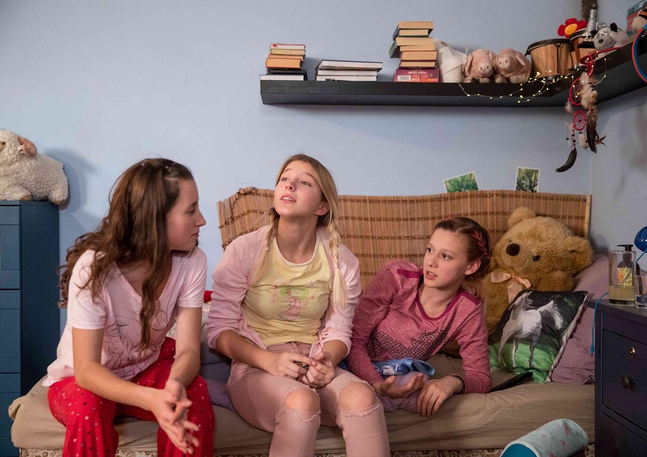 Drei Darstellerinnen, angezogen und frisiert wie Mädchen.