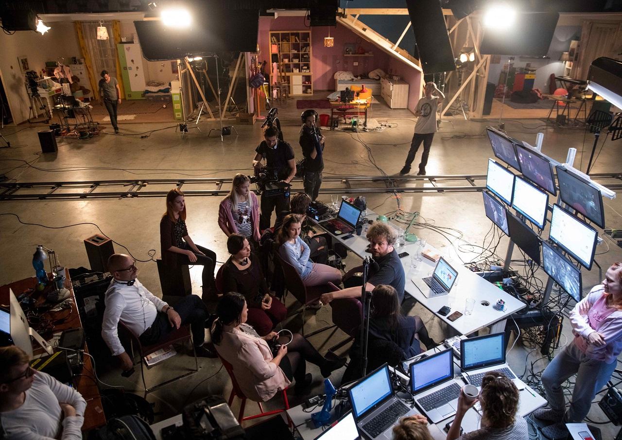 Filmstudio mit einem großen Team und Kulissen, die Kinderzimmer darstellen.
