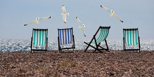 Vier gestreifte Liegestühle an einem Strand