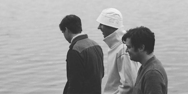 Die drei Bandmitglieder gehen ein Ufer entlang