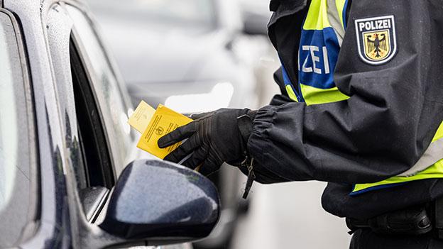 Polizist kontrolliert Impfpass