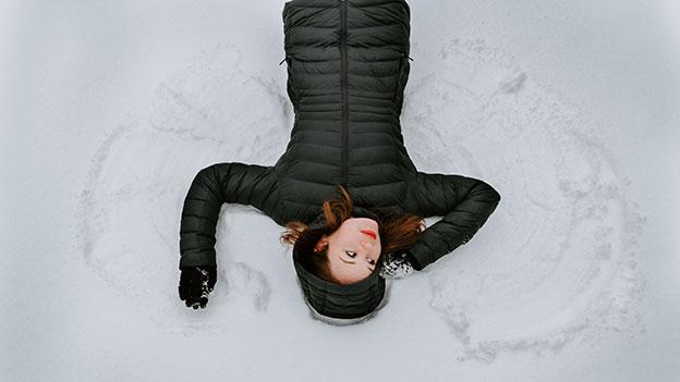 Frau in Dauenjacke liegt im Schnee